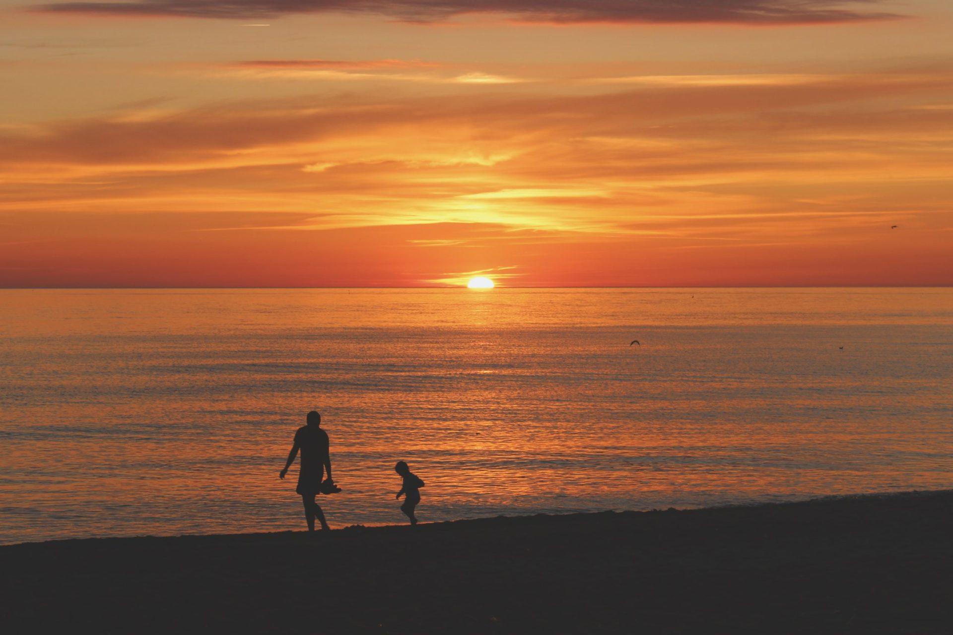 En vuxen och ett barn vis strandkant i solnedgång.